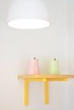Poterie douce sur l'étagère en bois avec la lampe d'illumination Photographie stock libre de droits