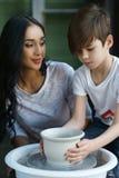 Poterie La jeune mère enseignent le fils Images stock