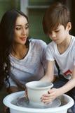 Poterie La jeune mère enseignent le fils Photographie stock
