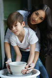 Poterie La jeune mère enseignent le fils Photo stock