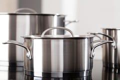 Potes de aluminio en el top de la cocina Fotos de archivo