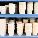 Potes de arcilla simples en estantes azules Fotografía de archivo