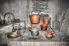 Potes de cobre viejos en una cocina rústica Fotos de archivo libres de regalías