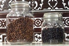 Potes de cristal que contienen diversos tipos de granos de café Fotografía de archivo libre de regalías