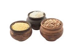 Potes de la loza de barro con los cereales aislados en el fondo blanco imagenes de archivo