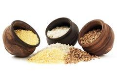 Potes de la loza de barro con los cereales en el fondo blanco imágenes de archivo libres de regalías