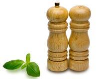 Potes de pimienta y potes de la sal con albahaca dulce Imagen de archivo libre de regalías