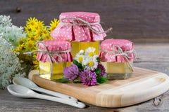 Potes líquidos frescos llenos de la miel con las flores salvajes del verano Imagenes de archivo