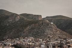 Pothia city on Kalymnos Island. View from the Pothia harbour to houses on the hillside and a small church high above the city royalty free stock photos