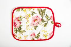 Potholder for hot dishes with white flowers and red border. A potholder for hot dishes with white flowers and red border royalty free stock image