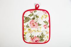 Potholder for hot dishes with white flowers and red border. A potholder for hot dishes with white flowers and red border royalty free stock images