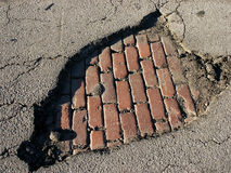 Pothole with bricks. Old brick pavement exposed by a pothole Royalty Free Stock Photos