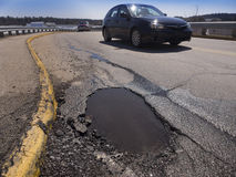 Pothole. Large deep pothole as an example of poor road maintenance due to cutbacks on the infrastructure budget Stock Image