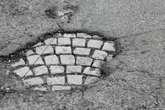 Pothole with old gray stone pavement Stock Photo