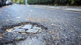 Pothole op kleine straat, royalty-vrije stock afbeeldingen