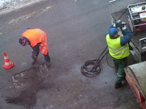 Pothole patching. Road menders at work; teamwork, hard work, power, blue-collar concept stock images