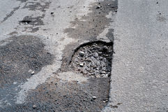 Pothole in road after spring thaw Royalty Free Stock Photography