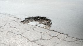 Pothole on the street - passing cars and trucks