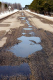 Potholes. And loose gravel in a paved road after the snow has thawed Royalty Free Stock Images