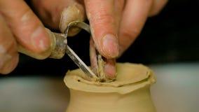 Potier professionnel découpant la tasse avec l'outil spécial dans l'atelier de poterie Image stock