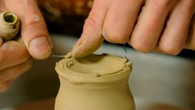 Potier professionnel découpant la tasse avec l'outil spécial dans l'atelier de poterie Photos stock