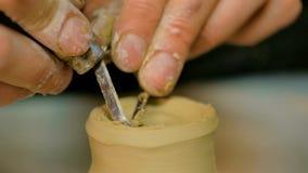 Potier professionnel découpant la tasse avec l'outil spécial dans l'atelier de poterie Photo stock