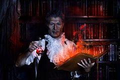 Potion. Crazy medieval scientist working in his laboratory with old manuscripts. Alchemist. Halloween Royalty Free Stock Photos