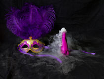 Potions and Magic. Smoke puffs from a bright pink chemical in a slender bottle like a magic potion, sitting next to a purple and gold plumed feather carnival Royalty Free Stock Images