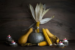 Potiron, épi de maïs, feuilles d'automne et bougies brûlantes de décoration o Photos libres de droits