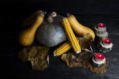 Potiron, épi de maïs, feuilles d'automne et bougies brûlantes de décoration o Photos stock