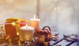 Potiron, cadeaux et bougies avec des feuilles d'érable Images stock