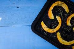Potiron coupé en tranches cru sur un plateau de cuisson Photos libres de droits