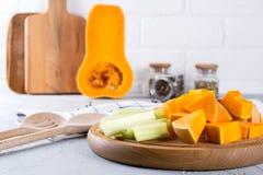 Potiron coupé en tranches sur un conseil en bois Nourriture de cuisine familiale avec le potiron Image libre de droits