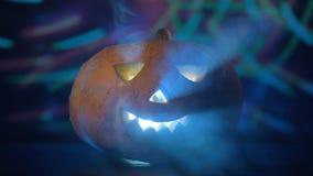 Potiron décoratif lumineux en nuages brumeux à une partie Potiron de Veille de la toussaint dans l'obscurité banque de vidéos