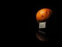 Potiron de Halloween avec le dollar sur le fond noir Photographie stock