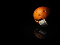 Potiron de Halloween avec le dollar sur le fond noir Photographie stock libre de droits