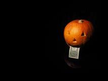 Potiron de Halloween avec le dollar sur le fond noir Image stock
