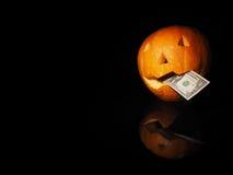 Potiron de Halloween avec le dollar sur le fond noir Photo stock