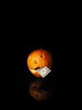 Potiron de Halloween avec le dollar sur le fond noir Image libre de droits