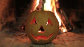Potiron de Halloween avec le visage effrayant sur le fond du feu clips vidéos