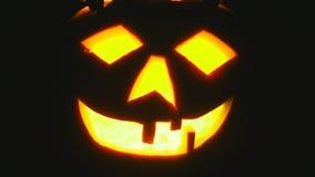Potiron de Halloween avec le visage effrayant avec avec une bougie brûlante banque de vidéos