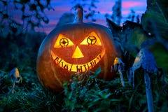Potiron de Halloween dans le jardin la nuit avec les yeux des vitesses de l'horloge avec les dents des pièces en métal photographie stock libre de droits