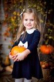 Potiron de participation de petite fille dans l'int?rieur d'automne photographie stock