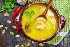 potiron de Soupe-purée avec des crevettes roses et des champignons de paris à bord de dessus Photos stock