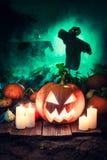Potiron effrayant sur le champ foncé avec des épouvantails pour Halloween Image libre de droits