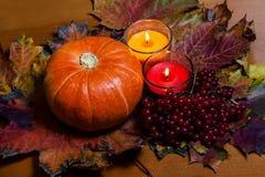 Potiron et bougies sur des feuilles d'automne Foyer sélectif Photo stock