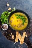 Potiron et soupe crème à légumes avec des graines, des tranches de pain et le persil de citrouille au-dessus d'un fond foncé avec image libre de droits