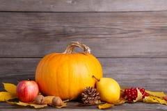 Potiron orange avec des feuilles et des légumes sur le gris photo stock