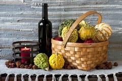 Potirons dans le panier avec la bouteille du vin rouge et de la bougie sur la texture Photographie stock