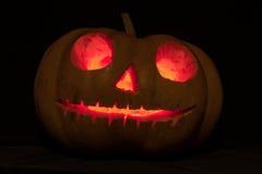 Potirons de Halloween avec le visage effrayant et la bougie brûlante sur b noir Image libre de droits